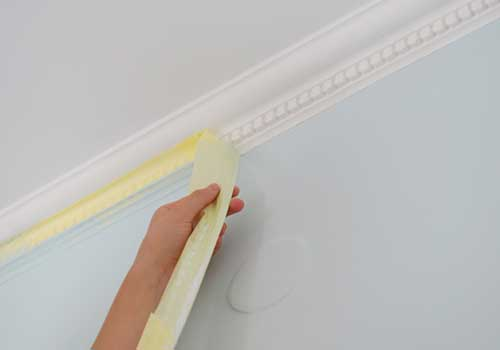 Applying Painters Tape to Baseboards